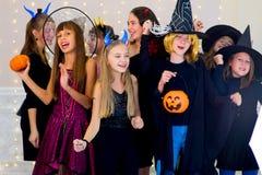 O grupo feliz de adolescentes dança em trajes de Dia das Bruxas fotos de stock royalty free