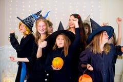 O grupo feliz de adolescentes dança em trajes de Dia das Bruxas fotografia de stock royalty free