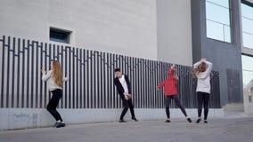 O grupo funky de dançarinos contemporâneos que fazem uma rua mostra junto vídeos de arquivo