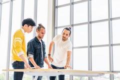O grupo multi-étnico de reunir-se de três homens discute o plano do projeto do clique junto, escritório moderno com o espaço da c foto de stock royalty free
