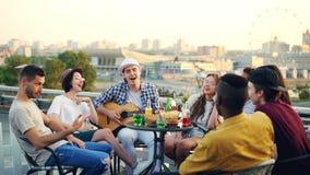 O grupo multirracial de jovens está cantando a música que senta-se no círculo no telhado quando o homem novo jogar a guitarra tab filme