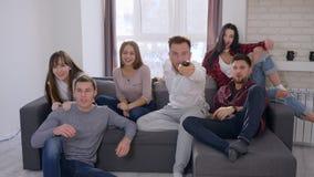 O grupo novo de amigos dos fãs corridos ao sofá e a volta na tevê para olhar o fósforo e a vitória então da comemoração dão altam video estoque