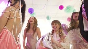 O grupo ofexcited os amigos fêmeas atrativos felizes novos que têm o divertimento que aprecia comemorando a festa de anos no salã filme