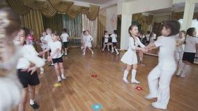 O grupo pequeno das crianças aprende a dança alegre ativa na classe vídeos de arquivo