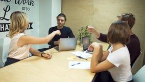 O grupo pequeno de empresários reune-se para discutir estratégias novas no negócio usando portáteis na sala de reunião do escritó filme