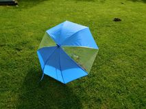 O guarda-chuva azul no jardim com montinho de terra Foto de Stock