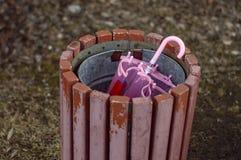 O guarda-chuva das crianças cor-de-rosa em uma urna no parque fotografia de stock royalty free