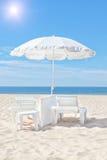 O guarda-chuva e o sol brancos bonitos de praia colocam em uma praia ensolarada. Imagens de Stock
