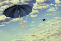 O guarda-chuva preto voa no céu dramático contra das nuvens brancas vitória fotos de stock
