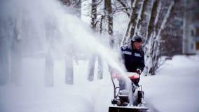 O guarda de serviço cancela a trilha com um snowplow no pátio de um prédio de apartamentos filme