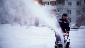 O guarda de serviço cancela a trilha com um snowplow no pátio de um prédio de apartamentos video estoque