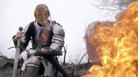 O guerreiro corajoso da mulher na armadura senta a inclinação na espada contra o fogo vídeos de arquivo