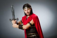 O guerreiro romano com a espada contra o fundo Foto de Stock