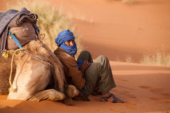 O guia do camelo do Berber toma uma ruptura Marrocos fotos de stock