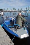 O guia não identificado da pesca amarra a visita de bicicletas a um barco de pesca no porto pelo lago Saimaa, Finlandia Imagens de Stock