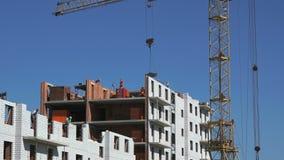 O guindaste de construção entrega um cimento para construtores filme