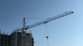 O guindaste de construção gerencie a seta no fundo da construção e do céu video estoque