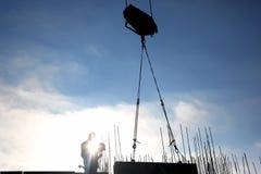 O guindaste de construção levanta a carga contra o sol imagem de stock royalty free