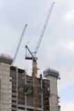 O guindaste e as construções estão no canteiro de obras Imagem de Stock Royalty Free