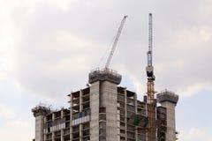 O guindaste e as construções estão no canteiro de obras Fotografia de Stock Royalty Free