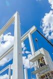 O guindaste móvel está operando-se à viga concreta do conjunto no edif novo Fotografia de Stock
