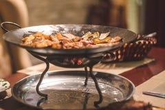 O guisado vegetal com carne serviu em um restaurante no vaso bonito do metal com carvões de incandescência Culinária oriental imagem de stock