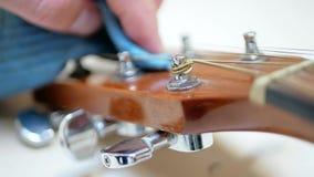 O guitarrista acústico limpa o instrumento musical espanando filme