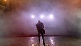 O guitarrista executa na fase Luz da fase, fumo video estoque