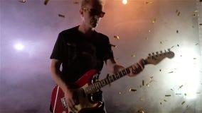 O guitarrista executa na fase Luz da fase, fumo De cima dos confetes dourados da queda video estoque