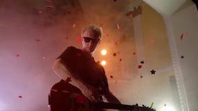 O guitarrista executa na fase Luz da fase, fumo De cima dos confetes dourados da queda vídeos de arquivo