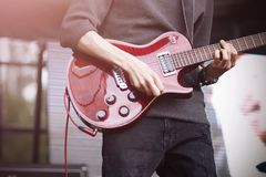 O guitarrista joga em uma guitarra el?trica vermelha na fase durante um concerto fotografia de stock