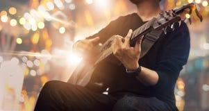 O guitarrista na fase e canta em um concerto para o fundo, fotografia de stock