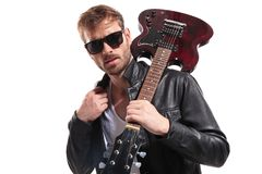 O guitarrista 'sexy' que veste óculos de sol guarda a guitarra no ombro foto de stock royalty free