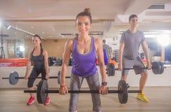 O gym de sorriso de três jovens torna mais pesado o homem das mulheres da barra Fotos de Stock
