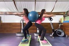 O gym do exercício de duas mulheres investe contra a bola do exercício do weightsgym da bola Fotos de Stock