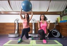 O gym do exercício de duas mulheres investe contra pesos da bola Fotografia de Stock Royalty Free