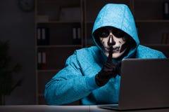 O hacker assustador que corta o guarda-fogo da segurança tarde no escritório imagens de stock