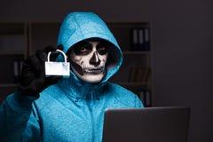 O hacker assustador que corta o guarda-fogo da segurança tarde no escritório fotografia de stock