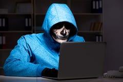 O hacker assustador que corta o guarda-fogo da segurança tarde no escritório imagem de stock royalty free