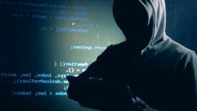 O hacker disfarçado está operando uma tabuleta ao lado de uma parede com dados projetados filme