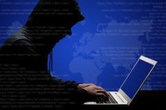 O hacker masculino perigoso em trabalhos hoody pretos duramente ao resolver o código em linha no laptop, informação da senha dos  foto de stock royalty free