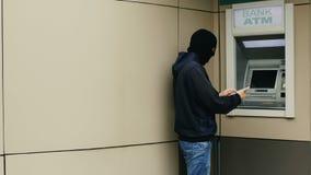 O hacker ou o ladrão com smartphone roubam a informação ou os dados do banco ATM imagem de stock
