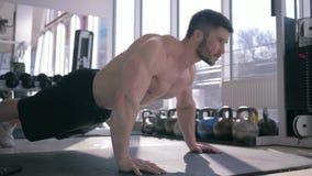 O halterofilismo, homem muscular do atleta com corpo de esportes bonito faz flexões de braço durante o exercício da força no gym video estoque