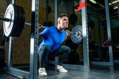 O halterofilista em um t-shirt azul aumenta uma barra que pesa 60 quilogramas no Foto de Stock Royalty Free