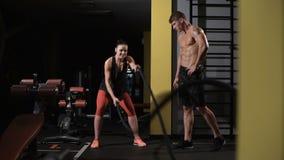 O halterofilista ensina a exercício sua amiga A jovem mulher atlética que faz algum crossfit exercita com uma corda video estoque