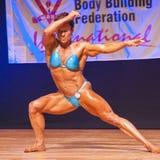 O halterofilista fêmea dobra seus músculos para mostrar-lhe o físico Imagens de Stock Royalty Free