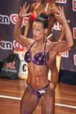 O halterofilista fêmea no bíceps dobro levanta e biquini roxo Fotografia de Stock Royalty Free