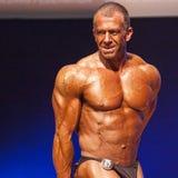 O halterofilista masculino dobra seus músculos e mostra seu melhor físico Imagens de Stock Royalty Free