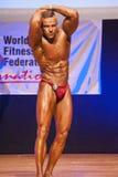 O halterofilista masculino dobra seus músculos para mostrar seu físico Imagem de Stock Royalty Free