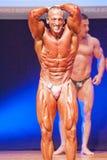 O halterofilista masculino dobra seus músculos para mostrar seu físico Fotos de Stock